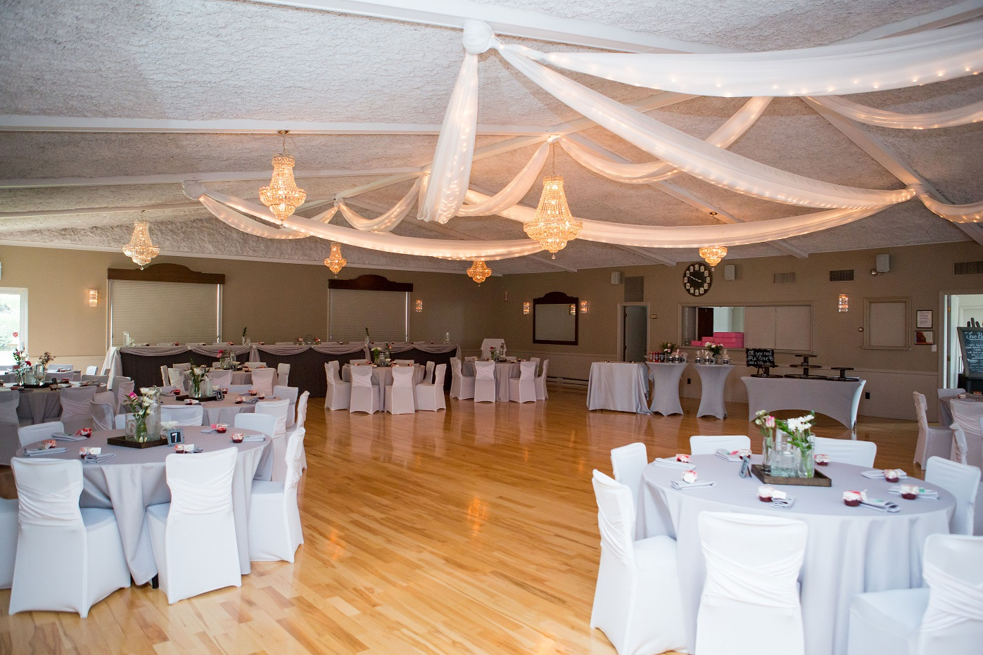room decorated for a wedding with tables and chairs covered in white linens and fabric streamers with twinkle lights hanging from the ceiling