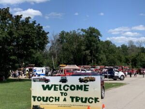 trucks in parking lot with welcome to touch a truck sign out front