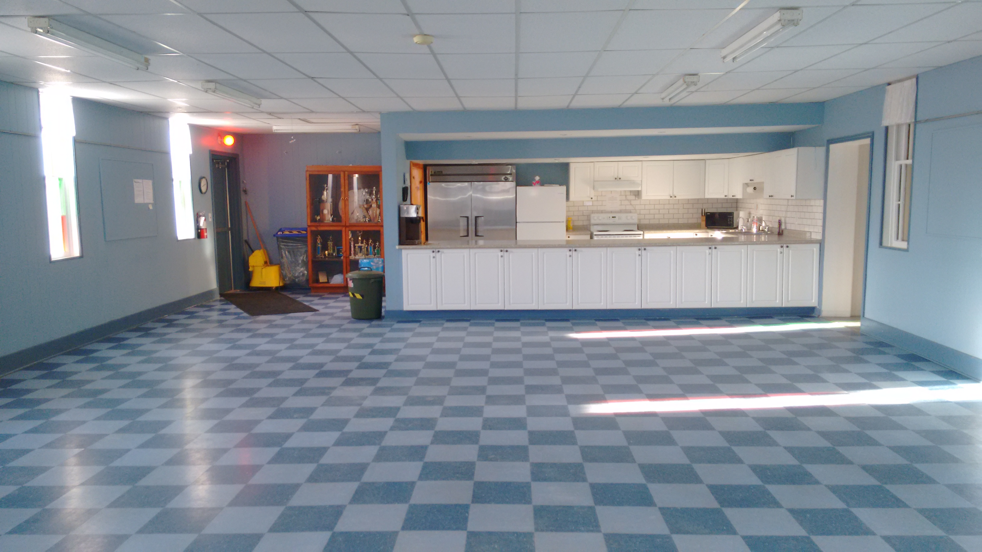 blue room with blue checkered floor and a kitchenette at the back of the room with a fridge, stove and cupboards