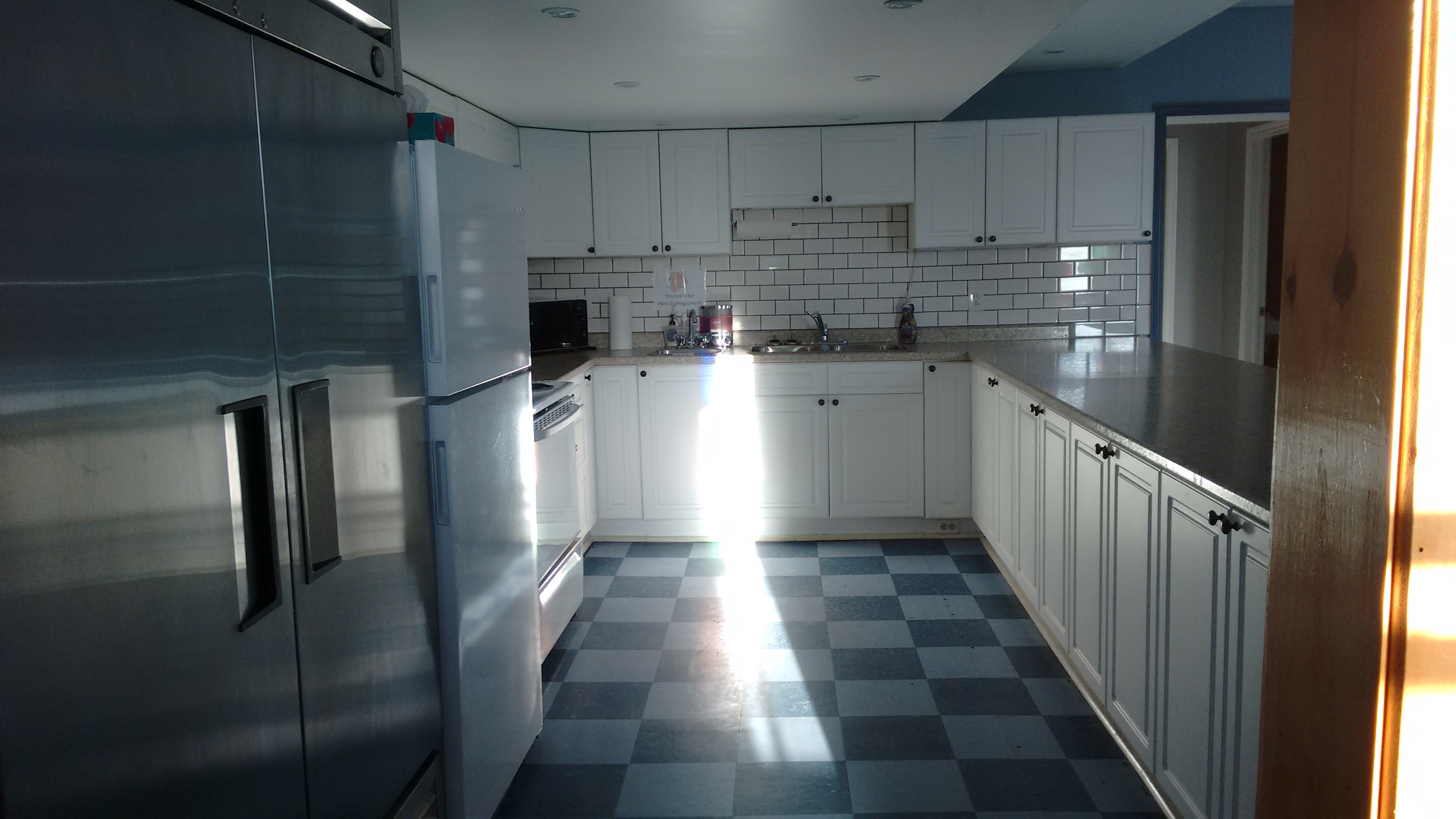 u-shaped room with 2 fridges, a stove, a sink and cupboards
