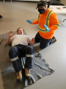 brad (lying on the floor) and steve (kneeling beside him) acting out a scenario