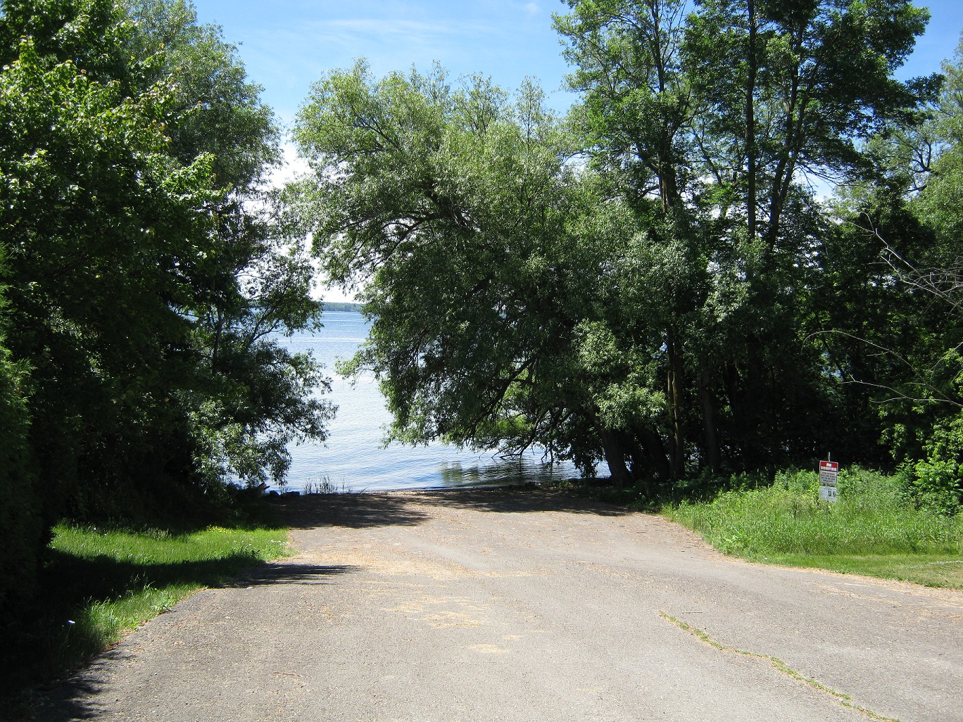 lane going into the st. lawrence river with big trees on either side