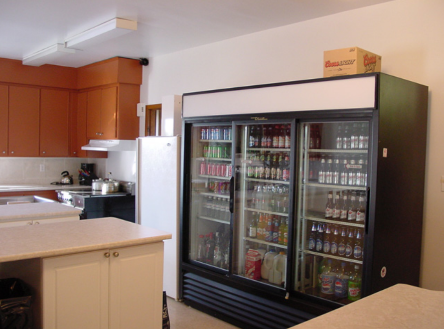 cooler fridge with 3 compartments, counters, stove, another fridge and cupboards