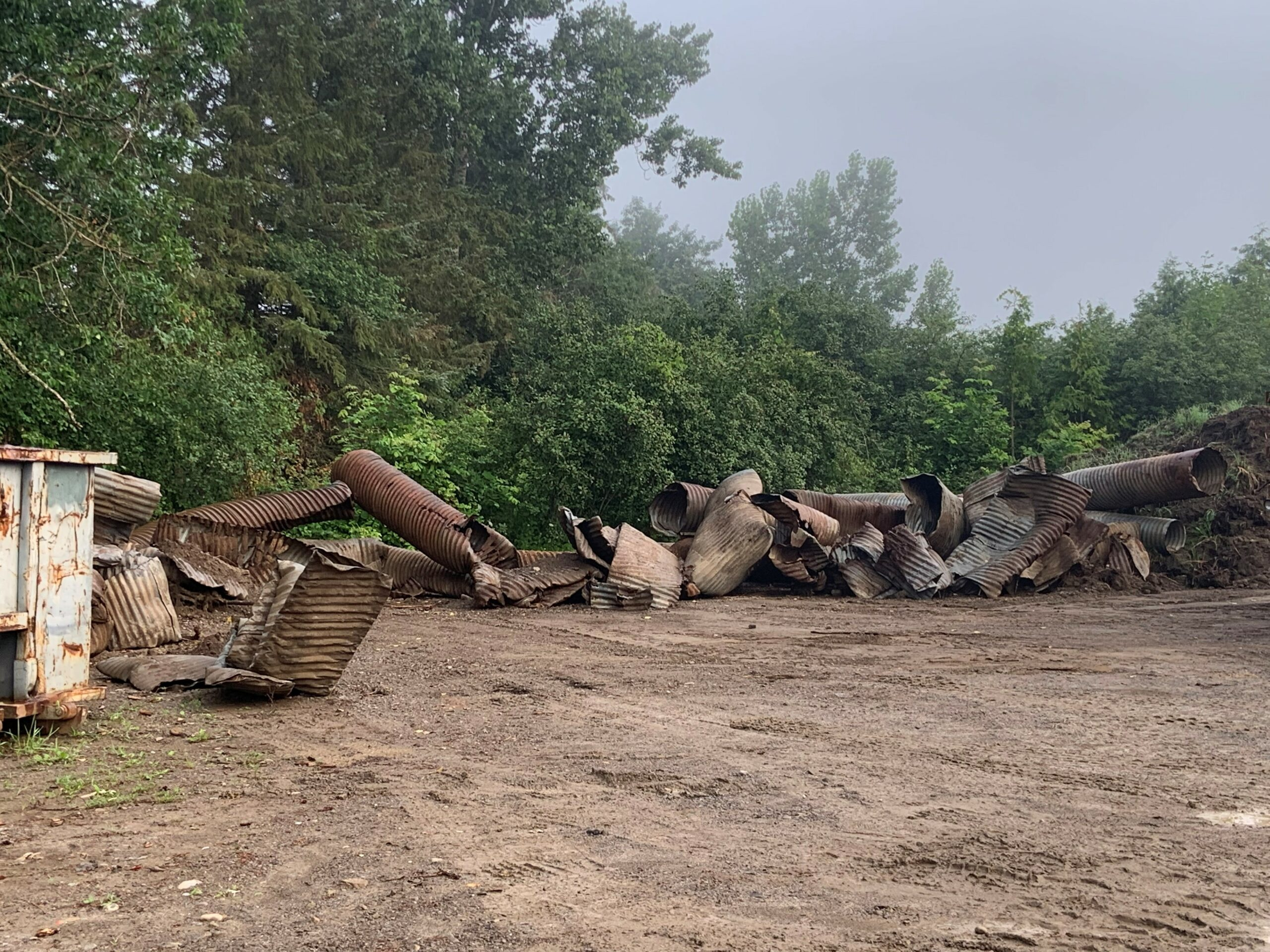 a big pile of old, dirty, rusted used culverts