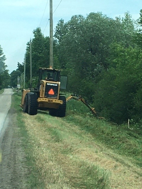 tractor cutting the long grass on the side of the township road